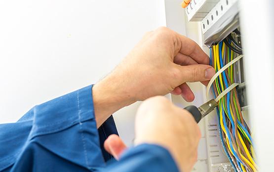 Ręce mężczyzny, który przecina przewody lub kable elektryczne
